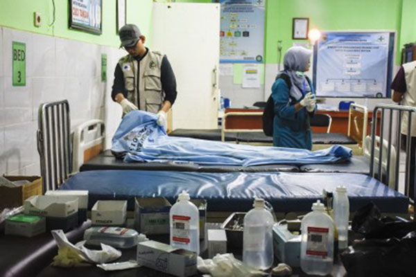 Petugas medis memerika kondisi korban meninggal dunia tertimbun longsor akibat gempa bumi, Tai Sieu Kim, 56 tahun, asal Malaysia, di Puskesmas Bayan, Tanjung, Lombok Utara, Nusa Tenggara Barat, pada Minggu (17/3/2019). - Antara/Ahmad Subaidi