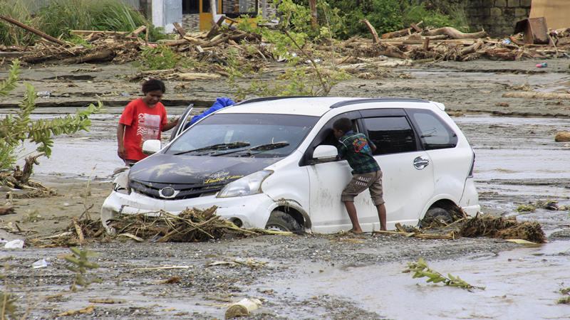 Kendaraan terendam lumpur saat banjir bandang di Sentani, Kabupaten Jayapura, Papua, Minggu (17/3/2019). - Antara
