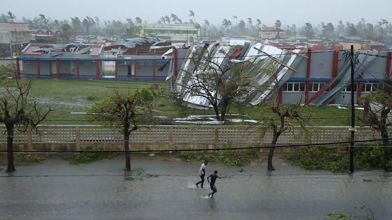 Orang-orang berjalan di jalan yang banjir di sebelah gedung-gedung yang dirusak oleh Topan Idai di Beira, Mozambik, 17 Maret 2019 dalam gambar diam ini diambil dari video media sosial pada 18 Maret 2019. - Reuters