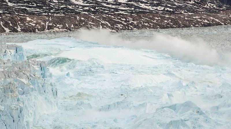 Air laut didorong ke atas oleh bagian bawah puncak gunung es saat jatuh kembali saat gletser besar di Helheim dekat Tasiilaq, Greenland, 22 Juni 2018. - Reuters