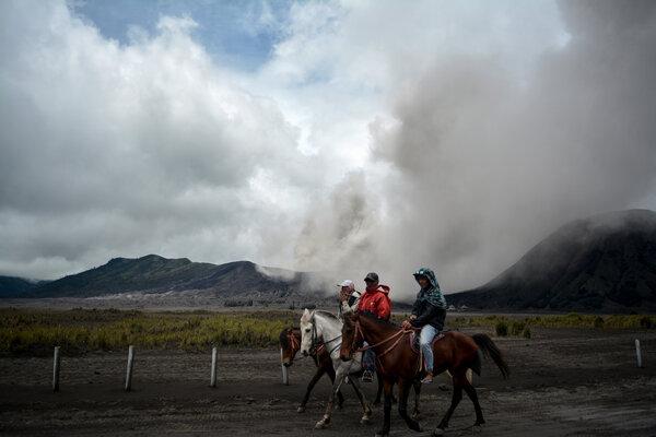 Tiga orang menunggang kuda dengan latar belakang Gunung Bromo yang menyemburkan abu vulkanis di Probolinggo, Jawa Timur, Jumat (15/3/2019). Gunung Bromo mengalami erupsi dan mengeluarkan material abu vulkanik dengan ketinggian asap hingga 700 meter dari kawah mengarah ke arah tenggara dengan status Gunung Bromo tetap level II atau Waspada dan gempa tremor didominasi amplitudo satu milimeter. - Antara/Umarul Faruq