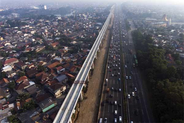 Ilustrasi - Kendaraan melintas di samping proyek kereta ringan atau Light Rail Transit (LRT) di jalan tol Jagorawi, Cibubur, Jakarta Timur, Rabu (24/5). - Antara/Sigid Kurniawan