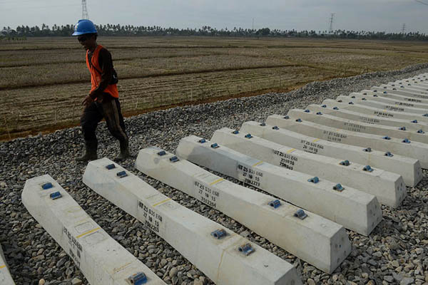 Ilustrasi - Pekerja melintasi bantalan jalur kereta Trans Sulawesi di Pekkae, Barru, Sulawesi Selatan. - Antara/Sahrul Manda Tikupadang