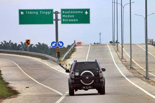 Pengendara melintas di proyek jalan tol Medan-Tebing Tinggi, di Serdang Bedagai, Sumatra Utara, Minggu (18/6/2017). - Antara/Irsan Mulyadi