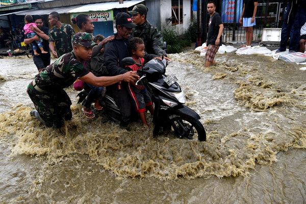 Prajurit TNI membantu seorang pengendara ketika berusaha menerobos banjir di Sentani, Jayapura, Papua, Kamis (21/3/2019). Hingga hari kelima pasca terjadinya banjir bandang, sejumlah ruas jalan utama masih terendam banjir dan sulit dilalui. - Antara/Zabur Karuru