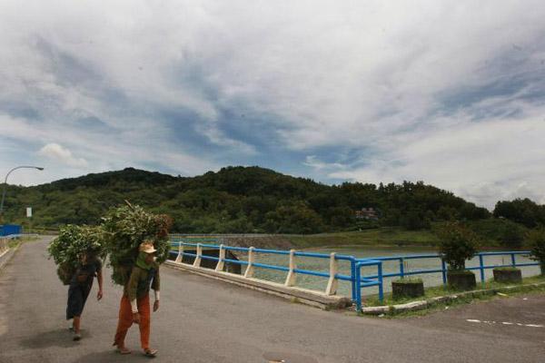 Warga menggendong hasil panen melintas di tepian Waduk Sermo, DI. Yogyakarta.JIBI - Desi Suryanto
