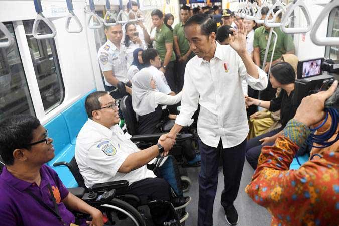 Presiden Joko Widodo menyalami penumpang difabel ketika mencoba MRT dengan rute stasiun Bundaran HI-Lebak Bulus-Istora di Jakarta, Kamis (21/3/2019). - ANTARA/Akbar Nugroho Gumay