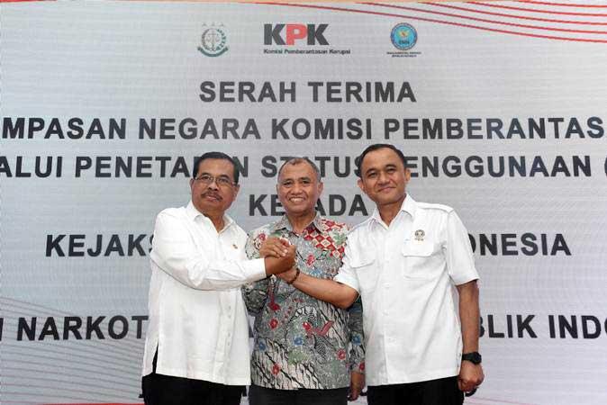 Ketua KPK Agus Rahardjo (tengah) berjabat tangan dengan Jaksa Agung Prasetyo (kiri) dan Kepala BNN Komjen Pol Heru Winarko (kanan) seusai penandatanganan berita acara serah terima barang rampasan negara oleh KPK melalui penetapan status penggunaan (PSP) kepada Kejaksaan Agung dan BNN di Gedung ACLC KPK, Jakarta, Rabu (20/2/2019). - ANTARA/Indrianto Eko Suwarso
