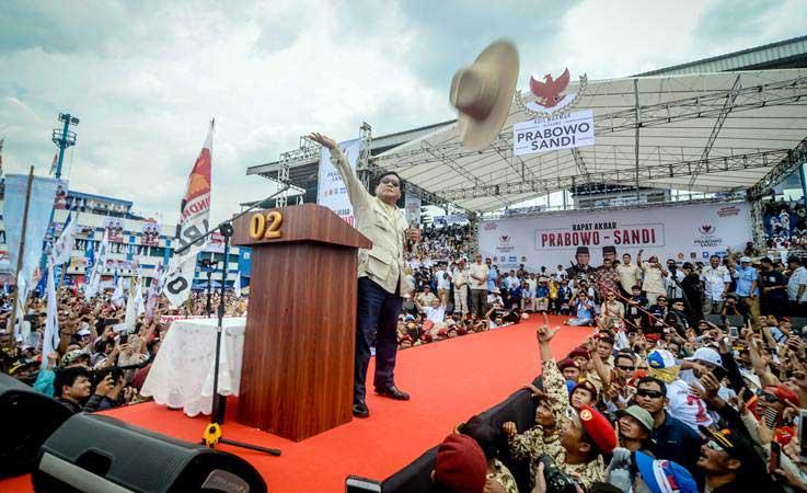 Capres nomor urut 02 Prabowo Subianto melemparkan topi kepada pendukungnya saat menghadiri kampanye akbar di Stadion Sidolig, Bandung, Jawa Barat, Kamis (28/3/2019). - ANTARA/Raisan Al Farisi
