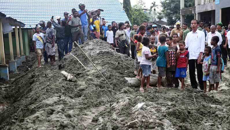 Presiden Joko Widodo (ketiga kanan) ditemani sejumlah bocah Papua mengunjungi area terdampak banjir bandang Sentani di Jayapura, Papua, Senin (1/4/2019). - ANTARA/Akbar Nugroho Gumay