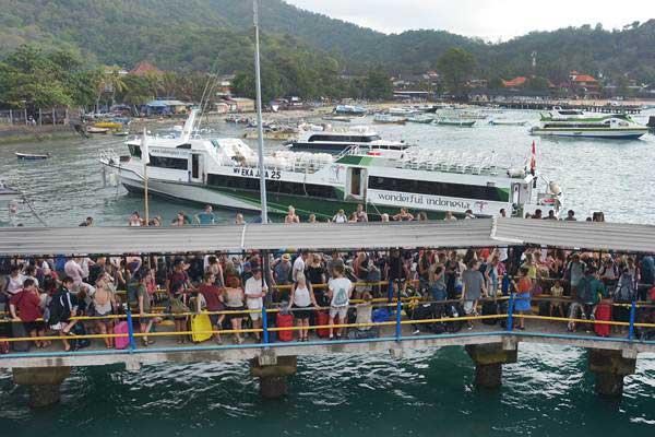 Sejumlah wisatawan calon penumpang menunggu jadwal keberangkatan kapal feri melalui Dermaga 2 Pelabuhan Padangbai, Karangasem, Bali, Jumat (20/7/2018). - ANTARA/Wira Suryantala