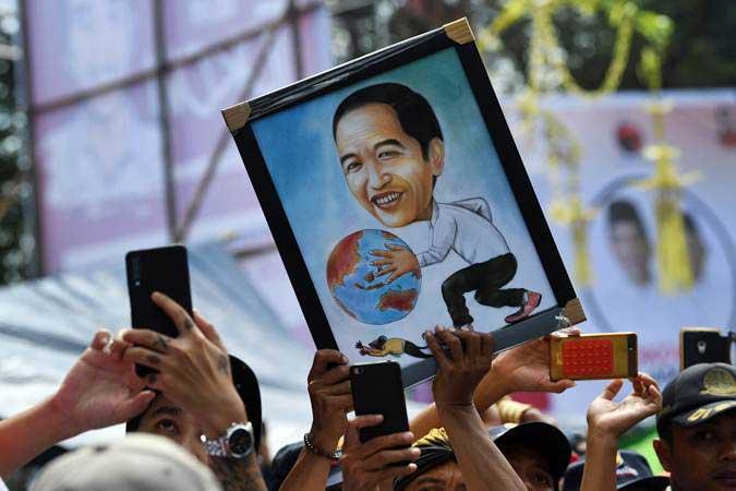 Pendukung membawa poster calon presiden nomor urut 01 Joko Widodo ketika kampanye terbuka di GOR Satria, Purwokerto, Banyumas, Jawa Tengah, Kamis (4/4/2019). - ANTARA/Wahyu Putro A