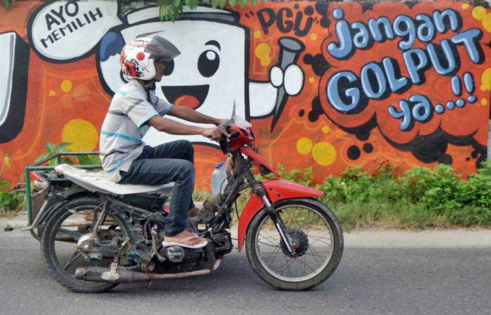 Pengendara melintas di depan mural (gambar dinding) tentang Pemilu 2019, di Jalan Samudera, Padang, Sumatra Barat, Selasa (12/2/2019). - ANTARA/Iggoy el Fitra