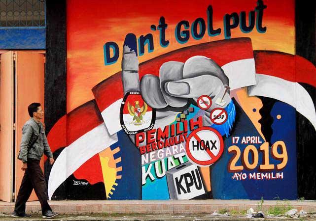 Warga melintas di depan mural tentang pemilu 2019 di Pasar baru Mamuju, Sulawesi Barat, Rabu (6/03/2019). - ANTARA/Akbar Tado