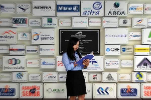 Karyawati berdiri di dekat logo beberapa perusahaan asuransi di kantor Asosiasi Asuransi Umum Indonesia di Jakarta, Senin (8/1). - JIBI/Dwi Prasetya