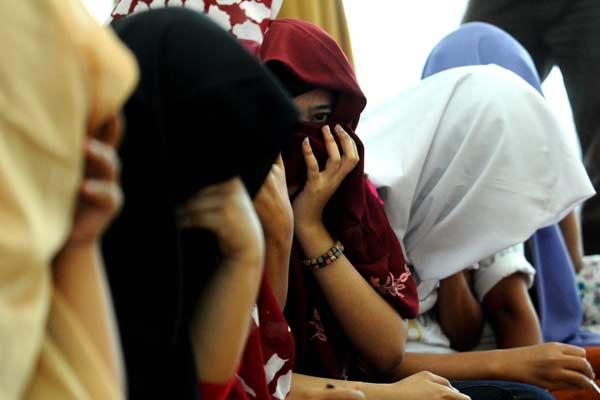 Sejumlah perempuan yang nyaris menjadi korban human trafficking atau perdagangan manusia menutupi mukanya dengan cadar. - Bisnis.com