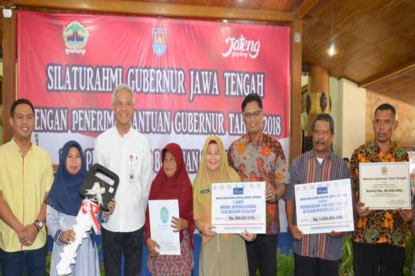 Gubernur Jawa Tengah Ganjar Pranowo (ketiga kiri) bersama Direktur Utama Bank Jateng Supriyatno (tengah) saat menyerahkan bantuan di Kabupaten Cilacap.