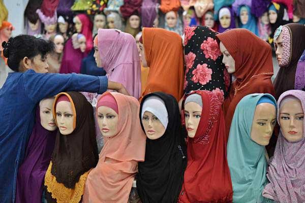 Pedagang menata jilbab dagangannya di salah satu gerai di sebuah pusat perbelanjaan di Semarang, Jawa Tengah, Selasa (30/5). - Antara/R. Rekotomo