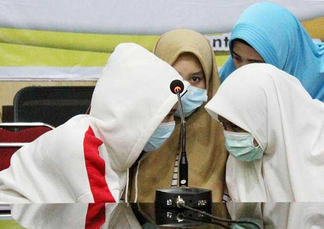Tiga dari 12 siswi SMU yang diduga menjadi pelaku dan saksi dalam kasus penganiayaan siswi SMP berinisial AU (14) berdiskusi dengan kerabat (kanan atas) di sela jumpa pers yang digelar di Mapolresta Pontianak, Kalimantan Barat, Rabu (10/4/2019). - ANTARA/Jessica Helena Wuysang
