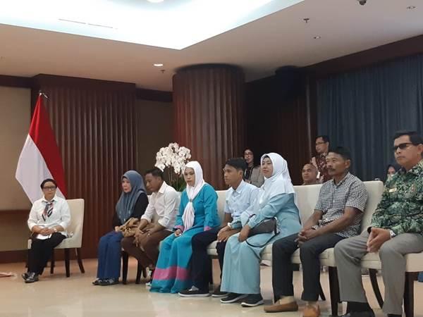 Menlu Retno Marsudi bersama keluarga WNI yang disandera Abu Sayyaf. Heri Ardiansyah (19) sandera yang bebas (kelima dari kiri, berbaju biru muda) duduk bersama mereka. - Bisnis/Iim Fathimah Timorria