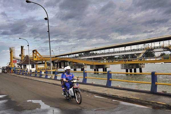 Ilustrasi - Pekerja melintas di area Proyek Pembangunan Dermaga 7 di Pelabuhan Merak, Banten, Kamis (30/11). - ANTARA/Asep Fathulrahman
