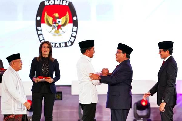 Pasangan capres-cawapres nomor urut 01 Joko Widodo (tengah) dan Ma'ruf Amin (kiri) bersalaman dengan pasangan nomor urut 02 Prabowo Subianto (kedua kanan) dan Sandiaga Uno (kanan) disela-sela debat pertama Pilpres 2019, di Hotel Bidakara, Jakarta, Kamis (17/1/2019). - Bisnis/Abdullah Azzam
