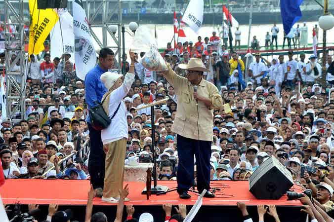 Calon Presiden nomer urut 02 Prabowo Subianto menerima sumbangan uang dari perwakilan emak-emak Palembang di hadapan pendukung dan simpatisan yang memadati pelataran Benteng Kuto Besak Palembang pada Kampanye akbar, di Palembang, Sumsel, Selasa (9/4/2019). - ANTARA/Feny Selly