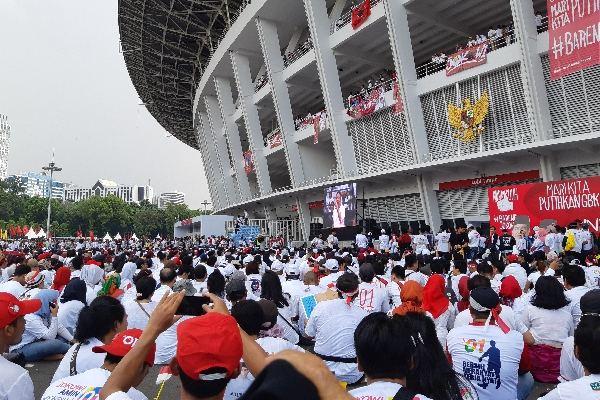 Massa Konser Putih bersatu yang lebih memilih duduk santai menanti Jokowi-Ma'ruf di sisi luar stadion GBK - Bisnis/Aziz Rahardyan