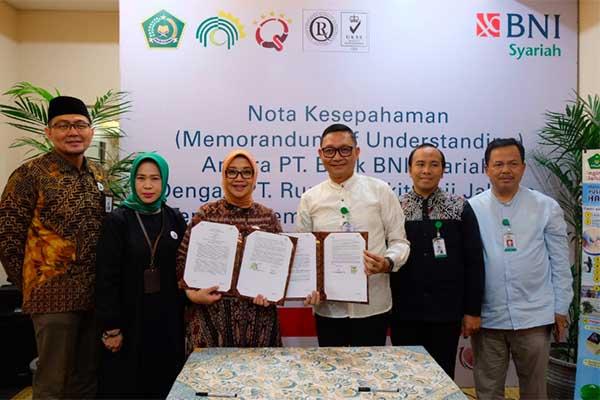 Penandatanganan nota kesepahaman BNI Syariah dengan RS Haji Jakarta terkait pemanfaatan produk dan jasa perbankan syariah di ruang pusat pelayanan terpadu kesehatan haji dan umrah (P2TKHU) RS Haji Jakarta, Jumat (12/4/2019). Penandatanganan ini dilakukan oleh Direktur Bisnis Komersial BNI Syariah Dhias Widhiyati (ketiga dari kiri) dan Direktur Utama RS Haji Jakarta Syarief Hasan Lutfie (ketiga dari kanan). - PT Bank BNI Syariah