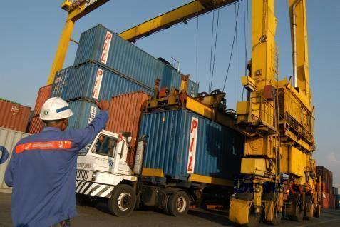 ilustrasi - Sebuah truk peti kemas melakukan pemindahan kargo (dooring) dari kapal kontainer. - bisnis.com