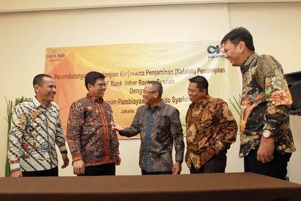 Direktur PT Bank Jabar Banten Syariah (BJBS) Dadang Iskandar (dari kiri), Direktur Indra Falatehan, Direktur Utama PT Jaminan Pembiayaan Askrindo Syariah Soegiharto, Senior Executive Vice President Supardi Najamuddin, dan Direktur Keuangan Subagio Istiarno, berbincang seusai penandatanganan kerja sama penjaminan (Kafalah) pembiayaan di Jakarta, Kamis (5/4/2018). - JIBI/Dwi Prasetya