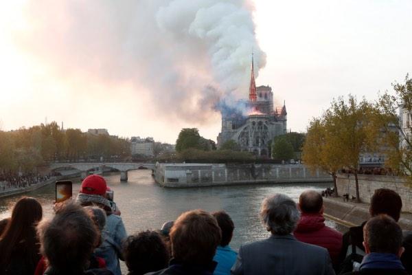Orang-orang melihat terbakarnya Katedral Notre-Dame dari kejauhan di Paris, Prancis, Senin (15/4/2019). - Reuters/Benoit Tessier
