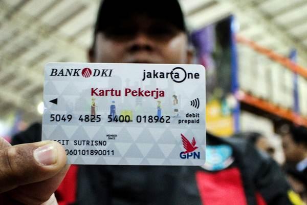 Pekerja menunjukkan Kartu Pekerja saat pendistribusian dan uji coba di Jakgrosir, Pasar Induk Kramat Jati, Jakarta, Senin (31/12/2018). - ANTARA/Putra Haryo Kurniawan