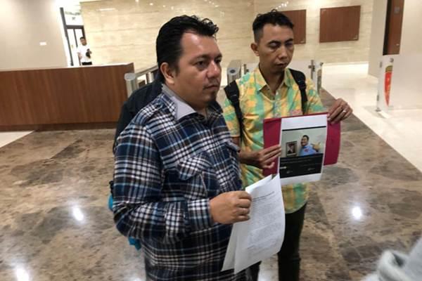 Ade Irfan Pulungan (kiri) membuat laporan ke Mabes Polri terkait video penurunan foto Presiden Jokowi. Tampak tangkapan layar berupa foto pria pada video dimaksud - Bisnis/Sholahuddin Al Ayyubi