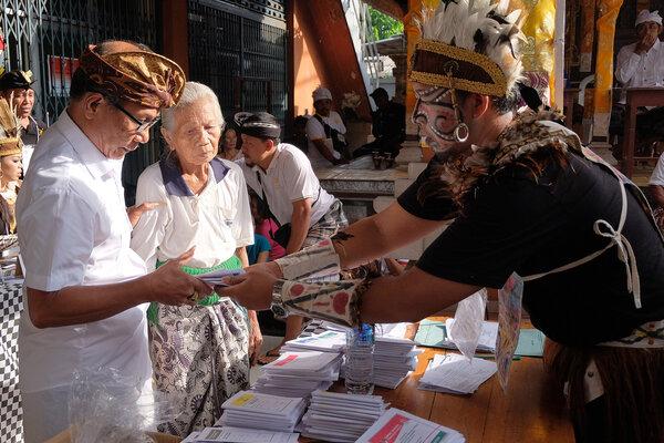 Anggota Kelompok Penyelenggara Pemungutan Suara (KPPS) yang berbusana adat Papua melayani warga saat pemungutan suara Pemilu serentak 2019 di TPS 18 Desa Penarungan, Badung, Bali, Rabu (17/4/2019). Anggota KPPS sengaja mengenakan busana adat nusantara untuk menjunjung persatuan dan kesatuan bangsa serta Pemilu damai. - Antara/Nyoman Hendra Wibowo