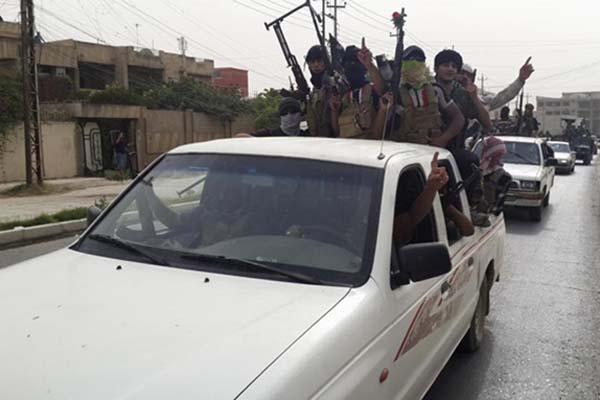 Tentara ISIS merayakan keberhasilan merebut kendaraan dari tentara Irak di dekat Kota Mosul - Reuters
