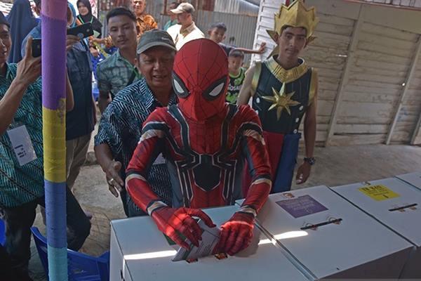 Pemilih menggunakan kostum Spiderman dan Gatotkaca menggunakan hak pilihnya di TPS 01 Kelurahan Pematang Kapau, Kota Pekanbaru, Riau, Rabu (17/4/2019). - Antara