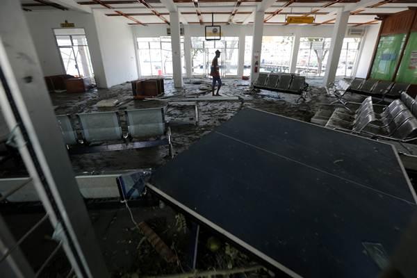 Pekerja berjalan di ruang tunggu terminal penumpang pelabuhan kelas-III Pantoloan yang rusak akibat gempa dan tsunami di Palu, Sulawesi Tengah, Senin (1/10). Pelabuhan Kelas-III Pantoloan kembali beraktivitas untuk melayani penumpang dan kapal yang membawa bantuan untuk korban bencana dari berbagai daerah. - Antara