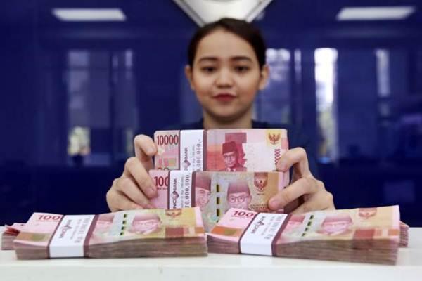 Karyawan memperlihatkan mata uang rupiah di salah satu bank di Jakarta. - JIIBI/Abdullah Azzam