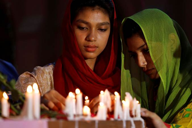 Warga menyalakan lilin untuk korban teror bom Sri Lanka, di  Peshawar, Pakistan, Minggu (21/4/2019). - Reuters/Fayaz Aziz