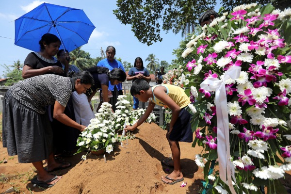 Keluarga menaruh bom di makam Rexy Duglas (67), tiga hari setelah serangkaian bom bunuh diri mengguncang 3 gereja dan 4 hotel pada Hari Paskah, di sebuah pemakaman dekat Gereja St. Sebastian, Negombo, Sri Lanka, Rabu (24/4/2019). - Reuters/Athit Perawongmetha