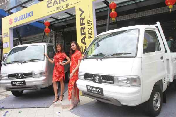 Model berdiri disamping mobil Suzuki New Carry Pick Up disela peluncurannya di Jakarta, Kamis (26/1). PT Suzuki Indomobil Sales , memperkenalkan produk terbarunya di segmen kendaraan niaga, New Carry Pick Up. Mobil ini dijual seharga Rp120,75 juta untuk varian flat deck dan Rp121,75 juta untuk varian wide deck. - Bisnis/Endang Muchtar