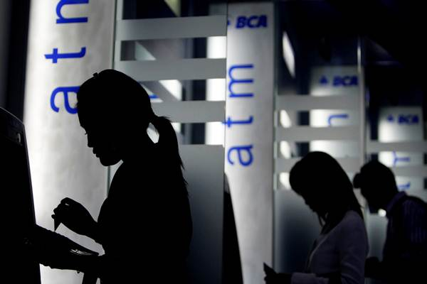 Nasabah melakukan transaksi di mesin ATM Bank BCA. - Reuters/Beawiharta