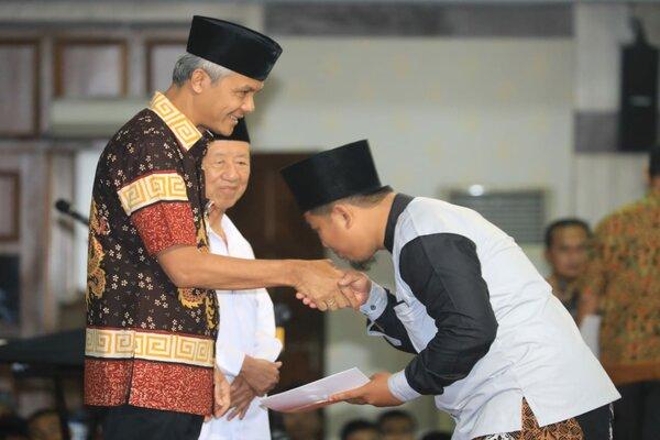 Gubernur Ganjar Pranowo menyerahkan santunan untuk keluarga petugas KPPS yang meninggal seusai bertugas di Pilpres-Pileg 2019, Jum'at (26/4). - Bisnis/Alif Nazzala R.