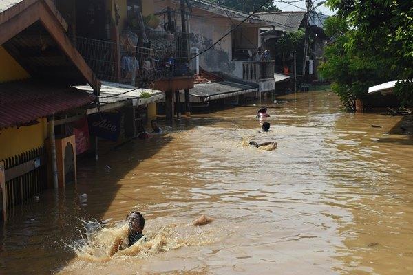 Sejumlah anak bermain air saat banjir melanda permukiman di kawasan Rawajati, Jakarta Selatan, Jum'at (26/4/2019). Banjir akibat curah hujan yang tinggi di kawasan Bogor itu mengakibatkan ratusan rumah di enam RT Kelurahan Rawajati terendam hingga mencapai ketinggian empat meter dan sejumlah warga diungsikan. ANTARA FOTO - Indrianto Eko Suwarso