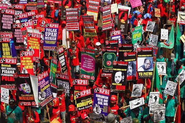 Massa membawa poster bertuliskan tuntutan di May Day. - JIBI/Dwi Prasetya