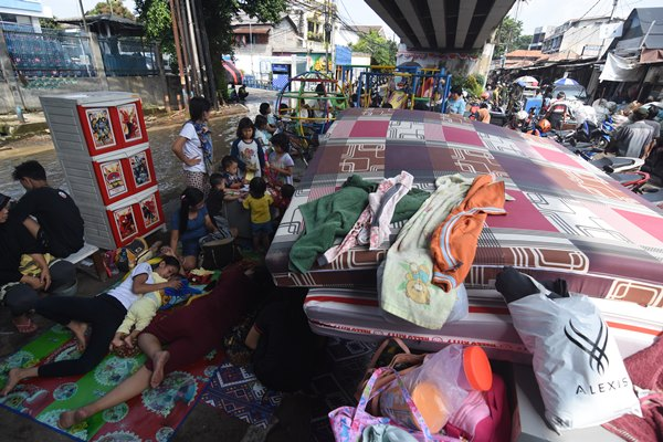 Warga terdampak banjir mengungsi di bawah flyover di kawasan Rawajati, Jakarta Selatan, Jum'at (26/4/2019). Banjir akibat curah hujan yang tinggi di kawasan Bogor itu mengakibatkan ratusan rumah di enam RT Kelurahan Rawajati terendam hingga mencapai ketinggian empat meter dan sejumlah warga diungsikan./ANTARA FOTO - Indrianto Eko Suwarso