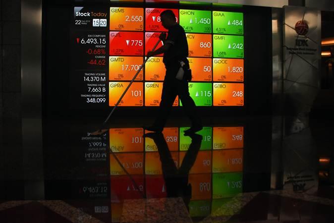 Pekerja melintas di depan layar pergerakan saham di Bursa Efek Indonesia, Jakarta, Jum'at (22/2/2019). - ANTARA/Indrianto Eko Suwarso