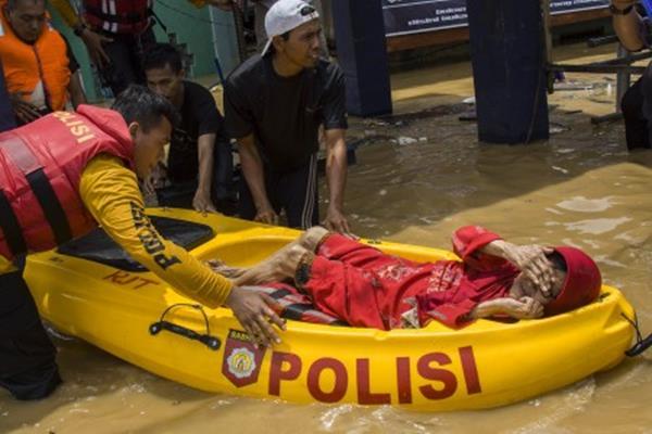 Petugas membantu evakuasi warga yang terdampak banjir di kawasan Kampung Pulo, Jakarta, Selasa (6/2). Kawasan tersebut terendam banjir akibat luapan air dari Sungai Ciliwung. ANTARA FOTO - Galih Pradipta