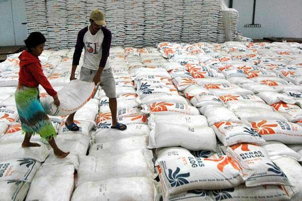 Pekerja mengangkat karung isi beras di Gudang Beras Bulog, Makassar, Sulawesi Selatan, Kamis (3/1/2019). - ANTARA/Abriawan Abhe